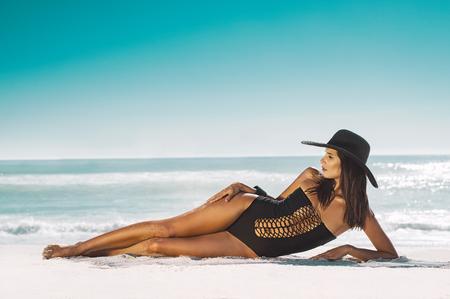 Arbeiten Sie junge Frau im schwarzen Badeanzug und im Strohhut um, die auf Seite am Strand liegt. Schönes gebräuntes Mädchen, das auf Sand liegt. Tragende Zauberbadebekleidung des attraktiven Mädchens auf tropischem Strand beim Ein Sonnenbad nehmen.