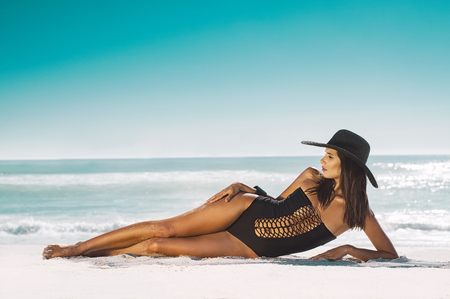Fashion young woman in black swimsuit and straw hat lying on side at beach. Beautiful tanned girl lying on sand. Attractive girl wearing glamour swimwear on tropical beach while sunbathing. Stock Photo