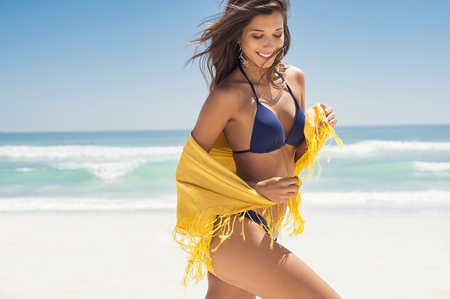 Young woman in bikini holding a yellow scarf on windy beach. Happy girl draped in yellow tissue and walking on beach with copy space. Cheerful woman enjoying summer while running at sea.