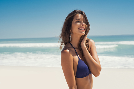 Portrait of young woman in blue bikini walking on tropical beach. Beautiful girl relaxing and enjoying vacation at sea. Smiling woman enjoying and thinking at seaside with copy space.