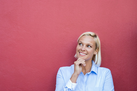 Closeup face of woman thinking with finger on chin. Happy pensive mature woman looking up and smiling on red wall with copy space. Portrait of blond thoughtful woman thinking isolated on red background.