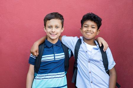 Beste kinderenvrienden die zich met hand op schouder bevinden tegen rode achtergrond. Gelukkig lachend klasgenoten staan samen op rode muur na school. Portret van multi-etnische schooljongens die van vriendschap genieten. Stockfoto