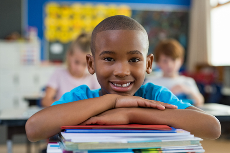 Portrait of african american schoolboy leaning on desk with classmates in background. Happy young kid sitting and leaning chin on stacked books in classroom. Portrait of elementary pupil looking at ca 写真素材