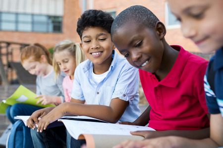 Multiethnic children sitting in a row and reading from notebook all together. School kid revising notes for exams sitting on the steps outside the elementary school. Latin school boy studying with friends before classwork.