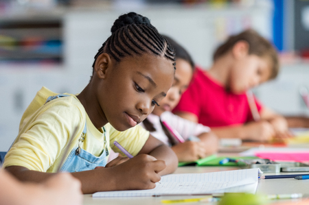 Cute pupil writing at desk in classroom at the elementary school. Student girl doing test in primary school. Children writing notes in classroom. African schoolgirl writing on notebook during the lesson. Stock Photo