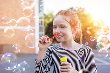 Portrait of lovely little girl with red hair blowing soap bubbles at park. Portrait of cute girl blowing soap bubbles outside the school. Happy female child playing with soap bubble at playground.