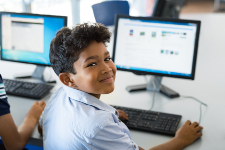 Young happy schoolboy using computer to search internet. Arab child learning to use computer at elementary school. Portrait of smiling middle eastern kid looking at camera while surfing the net in school library.