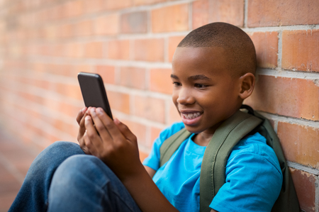 Happy african student wearing green bagpack and using smartphone at school. Smiling cute boy playing with smart phone while sitting on floor. Cheerful child making video conversation on cell phone.