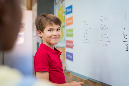 Clever boy doing sums on white board and looking at camera. Smiling schoolboy solving addition and subtraction sum in mathematics lesson. Proud young boy standing with math operation solved.