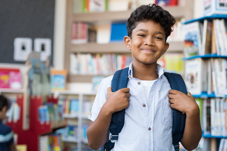 Portrait of smiling hispanic boy looking at camera. Young elementary schoolboy carrying backpack and standing in library at school. Cheerful middle eastern child standing with library background. Stock Photo - 100140800