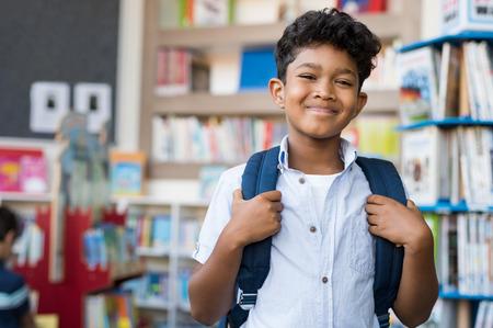Portret uśmiechający się chłopiec hiszpanin patrząc na kamery. Młody uczeń podstawowa niosąc plecak i stojąc w bibliotece w szkole. Wesoły Bliskiego Wschodu dziecko stojące z tłem biblioteki.
