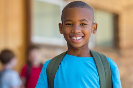 Ragazzo di scuola afroamericano sorridente con lo zaino che guarda l'obbiettivo. Allegro ragazzo nero che indossa uno zaino verde con un grande sorriso. Istruzione elementare e primaria.