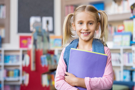 Portrait of cute blonde girl with pigtails holding books and wearing backpack at library. Closeup face of little primary schoolgirl looking at camera with satisfaction. Portrait of happy smiling female child. 写真素材