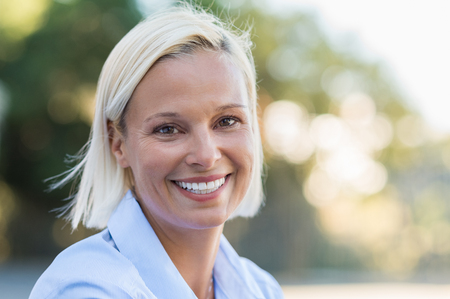 Portrait of mature woman smiling and looking at camera outdoor. Closeup face of a middle aged woman smiling at park. Blond mid woman relaxing in the lawn in a summer day. Standard-Bild