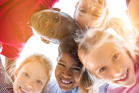 Portrait of happy kids in circle looking down and embracing. Group of five multiethnic friends outdoor looking at camera and smiling. Closeup face of smiling children looking down at the camera together at park.