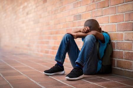 Jeune garçon assis seul avec un sentiment de tristesse à l'école. Enfant africain déprimé abandonné dans un couloir et appuyé contre un mur de briques. Concept d'intimidation, de discrimination et de racisme à l'école avec espace de copie. Banque d'images - 103854710