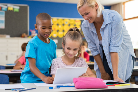 Multiethnic young students using digital tablet in classroom with teacher. Teacher in class with kids using electronic tablet. Teacher teaching how to use electronic device to children at elementary school. Stock Photo