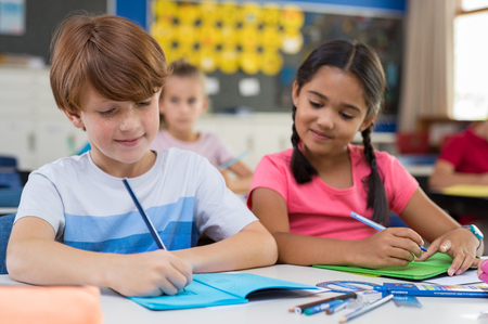 Hispanic school girl looking in boys book while classmate writing. Elementary children in classroom writing exam while girl copy from classmate. Portrait of cute girl and boy taking notes during less