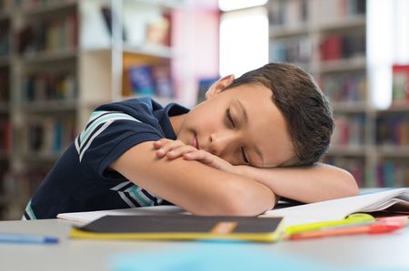 Young boy sleeps on library desk. Tired pupil fell asleep while studying on table with books. Cute child lying on books and sleeping in class during lesson. Sleepy schoolboy at school. Archivio Fotografico