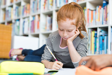Young girl lying on floor and drawing on copybook. Cute school girl doing homework at library. Little female child writing on notebook while lying on floor at school with books in background. Banque d'images - 103854753