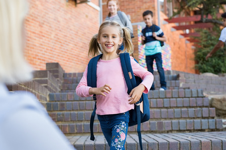 Happy cute girl running with stretched arms towards mother after school. Young school child feeling happy after lesson at primary school. Elementary student kids running into mothers hands to hug her after school. Banco de Imagens