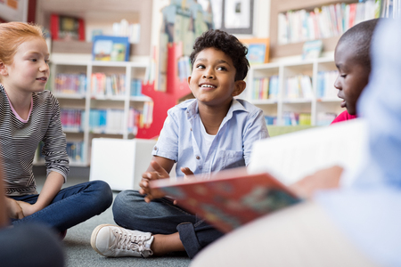 Multiethnic group of kids sitting on floor in circle around the teacher and listening a story. Discussion group of multiethnic children in library talking to woman. Portrait of smiling hispanic boy in elementary school.