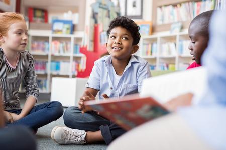 Groupe multiethnique d'enfants assis sur le sol en cercle autour de l'enseignant et écoutant une histoire. Groupe de discussion d'enfants multiethniques dans la bibliothèque parlant à une femme. Portrait de garçon hispanique souriant à l'école primaire. Banque d'images - 103854763
