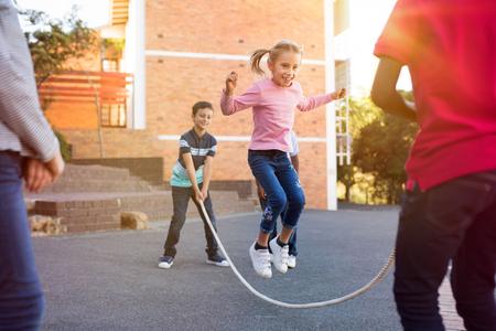 Glückliche Grundschulkinder, die zusammen mit Springseil im Freien spielen. Kinder, die Springseilsprungspiel spielen und draußen lachen. Glückliches süßes Mädchen, das über Springseil springt, das von ihren Freunden gehalten wird. Standard-Bild