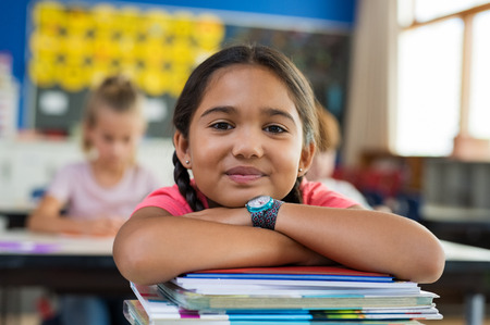 Portrait of cute little schoolgirl leaning on stacked books in classroom. Happy young latin girl in casual keeping chin on notebooks. Closeup face of smiling girl at elementary school.