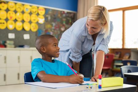 Teacher helping young african boy with homework. Happy teacher helping her student at elementary school. Portrait of woman teaching to schoolchild in classroom. Elementary school teacher helping students. Stock Photo