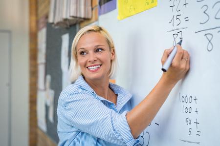 Leraar leert rekenen op whiteboard in de klas. Glimlachende blonde vrouw die toevoegingen in kolom in klasse uitlegt. Wiskundeleraar die rekensommen uitlegt aan elementaire kinderen. Stockfoto