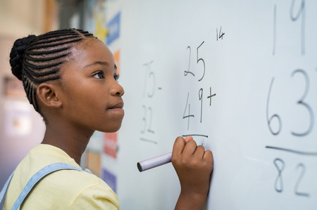 Portrait de fille africaine solution d'écriture de sommes sur tableau blanc à l'école. Écolière noire résolvant la somme d'addition sur un tableau blanc avec un marqueur. Enfant de l'école pensant tout en faisant un problème de mathématiques. Banque d'images - 100140914