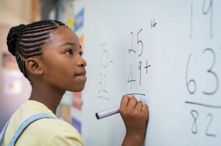 Retrato de niña africana escribiendo solución de sumas en la pizarra en la escuela. Colegiala negra resolviendo suma de suma en pizarra blanca con rotulador. Niño de la escuela pensando mientras hace problemas de matemáticas.