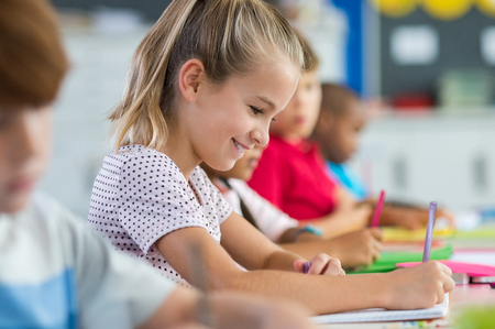 Smiling scholar girl sitting with other children in classroom and writing on textbook. Happy student doing homework at elementary school. Young schoolgirl feeling confident while writing on notebook. Stock Photo