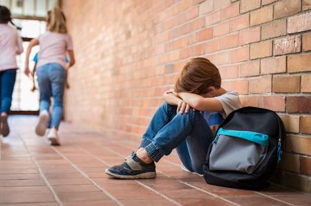 Petit garçon assis seul sur le sol après avoir subi un acte d'intimidation pendant que les enfants courent en arrière-plan. Triste jeune écolier assis sur le couloir avec les mains sur les genoux et la tête entre ses jambes. Banque d'images - 100140941
