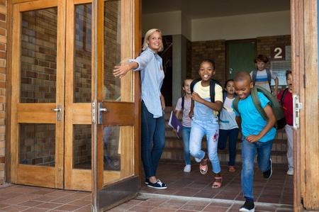 微笑的小学儿童愉快回家。快乐的学校女孩和男孩戴着背包和在课程结束时跑在学校外面。老师抱着门,而学生跑了出去。