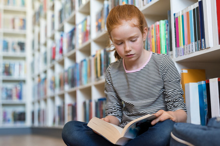 Elementary schoolgirl reading a book at the library. Cute young girl with red hair sitting on floor and reading a book. Diligent pupil concentrated in reading book. Reklamní fotografie