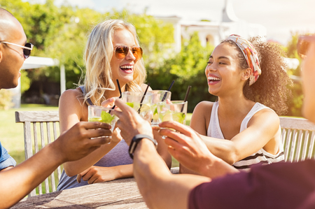 Two happy young couples toasting with glasses of cocktails. Young beautiful women and men drinking lemonade and smiling. Stock Photo