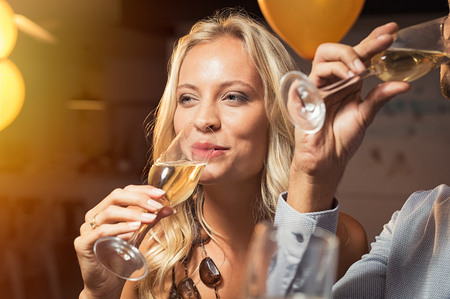 Young woman holding white wine glass and taking a sip. Closeup face of beautiful blond girl enjoying party at nightclub and drinking champagne. Portrait of woman feeling good with sparkling glass of champagne.