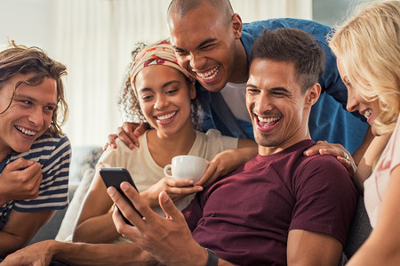 Joyful man showing video on his mobile phone with friends as they sit together and laugh. Group of cheerful young men and women laughing while looking at smartphone at home.