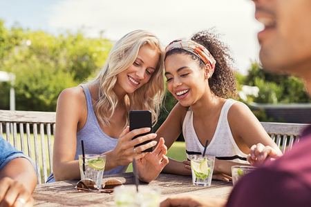 Two young women looking at smart phone and smiling sitting at table outdoor. Happy multiethnic girls taking selfie at outdoor cafeteria.