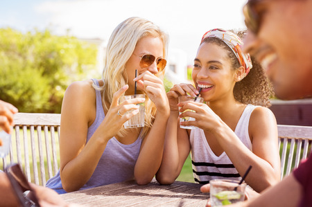 Young women gossiping outdoor and drinking lemon juice. Cheerful multiethnic girls laughing and sitting at outdoor café. Friends having fun together during summer vacation.