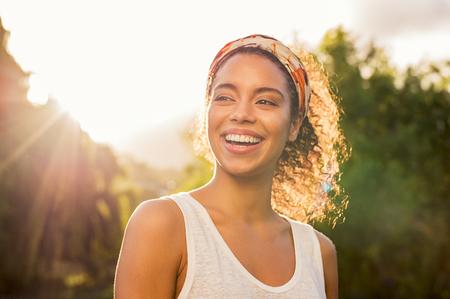 Portret van mooie Afro-Amerikaanse vrouw glimlachend en weg kijken naar park tijdens zonsondergang. Openluchtportret van een glimlachend zwart meisje. Gelukkig vrolijk meisje lachen om park met gekleurde haarband.