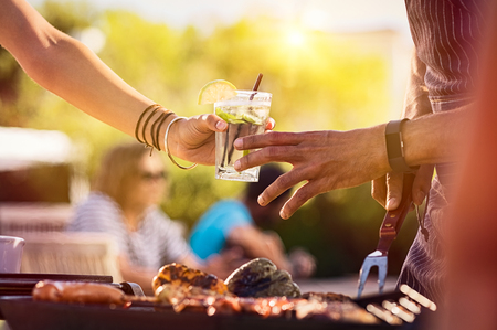 Closeup of young woman hand passing a drink to a man while preparing barbeque. Girl sharing glass with fresh lime juice during outdoor bbq. Stock fotó