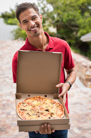 Young delivery man in red uniform holding a pizza. Portrait of happy delivery boy showing pizza in a cardboard box. Stock Photo