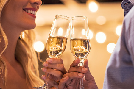 Man and woman toasting champagne flutes under light bulb outdoor. Closeup of boyfriend and girlfriend hands toasting glasses of white wine to celebrate their anniversary.