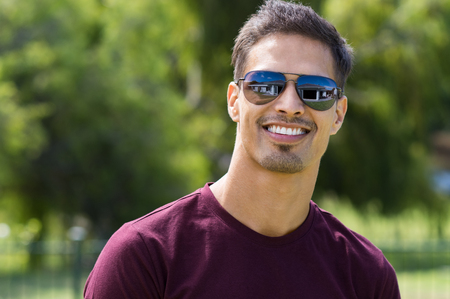 Young man wearing sunglasses outdoor. Cheerful guy looking at camera with glasses looking at camera at park. Latin man enjoying summer.