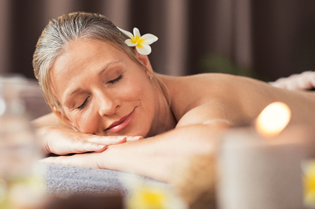 Beautiful blond woman relaxing at spa after body massage. Portrait of mature woman lying on massage table with closed eyes. Senior woman lying on a lounger at wellness center with candles.