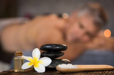 Closeup of stacked black hot stones on wooden table with oil, rock salt and frangipani flower. Zen stones in spa center with cosmetics and massage products. Wellness, beauty and wellbeing concept. Stockfoto