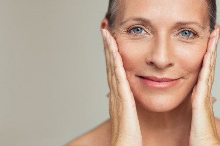 Portrait of beautiful senior woman touching her perfect skin and looking at camera. Closeup face of mature woman with wrinkles massaging face isolated over grey background. Aging process concept. Stock Photo